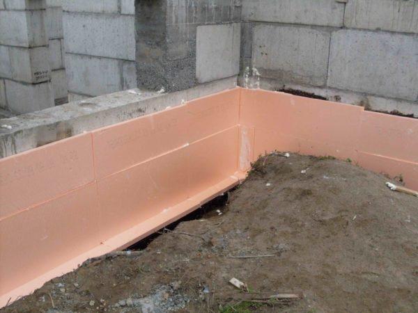 Фундамент оклеивается Пеноплексом, пока мастика еще не засохла