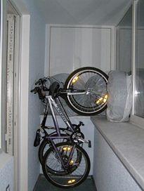 Вертикальное положение велосипеда на застекленном балконе