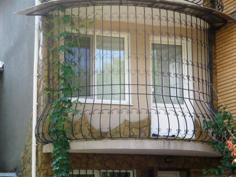 Балкон с кованой решёткой на первом этаже