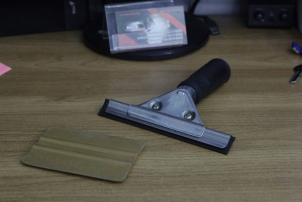 Резиновыми шпателями разравнивают наклеенный материал