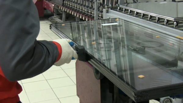 Сборка стеклопакета. Чтобы обеспечить адгезию герметика, мягкое энергосберегающее напыление приходится зачищать вдоль всей кромки.